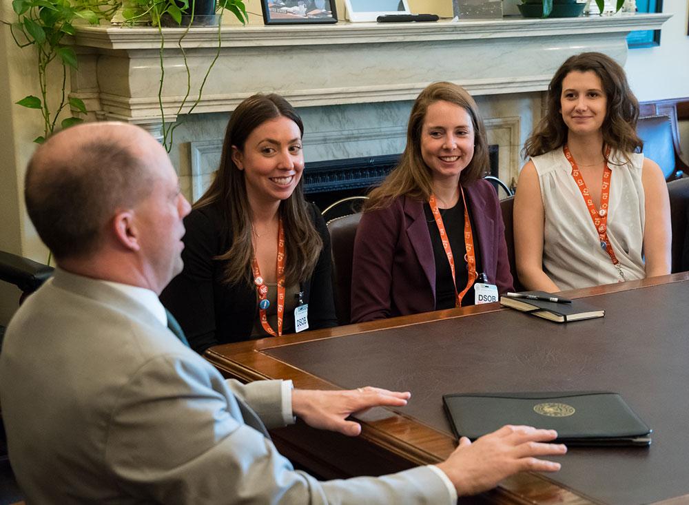 Three female CARE advocates sit at a table with a male legislator.