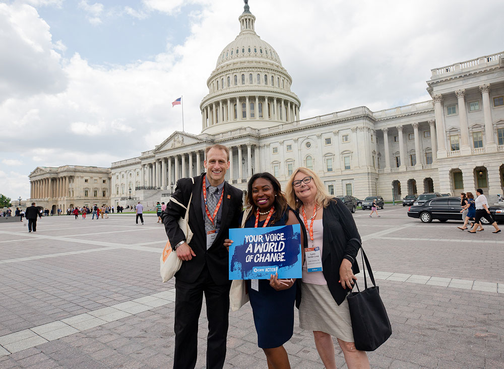 Three CARE advocates stand in front of the US Capitol building. One is holding a blue CARE Action sign that says,